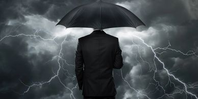A man wearing a suit and holding an open umbrella with a dark sky and lightening storm in the background