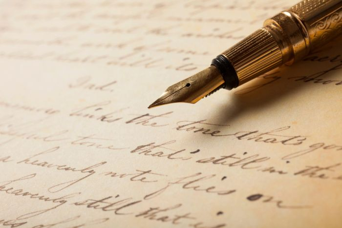 antique gold pen on beige manuscript with cursive script