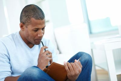 For screenreaders - an image of an African American man sitting, holding a pen and personal planner