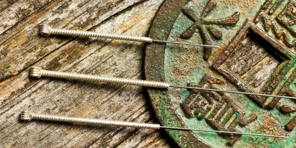 acupuncture needles on i ching coin