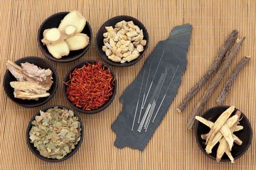 Small bowls of chinese herbs, acupuncture needles on a flat stone, all on a reed mat