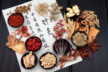 Assortment of chinese herbs on parchment paper with chinese lettering