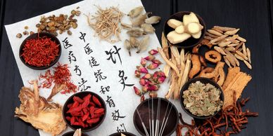 Chinese medicine calligraphy with raw Chinese herbs and acupuncture needles.