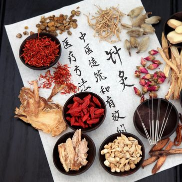 A variety of Chinese herbs in bowls against a background of paper with Chinese writing on it.