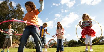 Children practice hula-hooping to improve their physical literacy