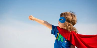 Little girl super hero wearing a blue mask and red cape and looking determined
