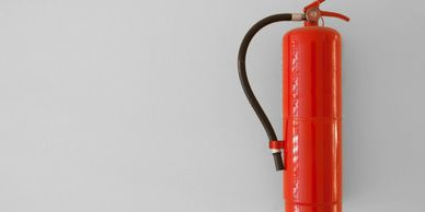 Red fire extinguisher hanging on a wall