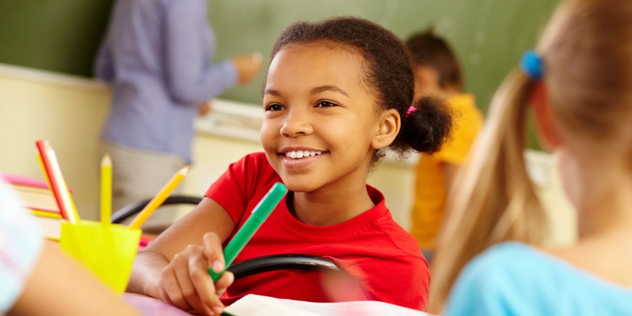 This is a picture of a young girl smiling as she sits in a classroom with her classmates.