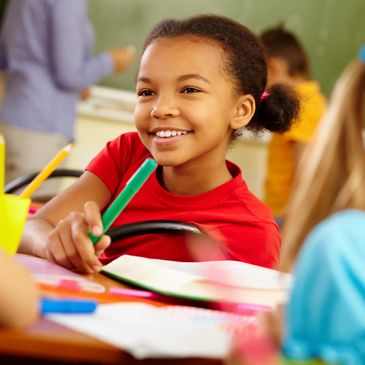 Little girl smiling in a classroom