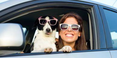 Woman and dog in a car with sunglasses.