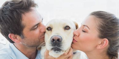 Man and woman kissing a dog