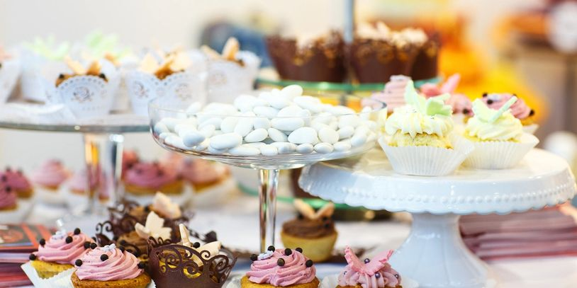 A table set with assorted desserts on cake stands. Cupcakes and cakes.