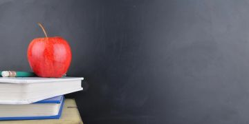 An apple sits atop a pile of books, with a blank chalkboard background