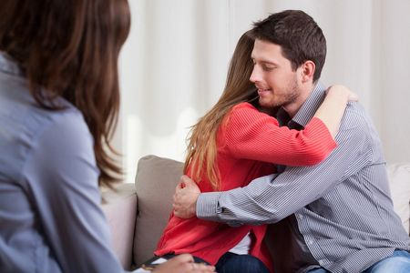 Young couple in marriage counseling embracing.