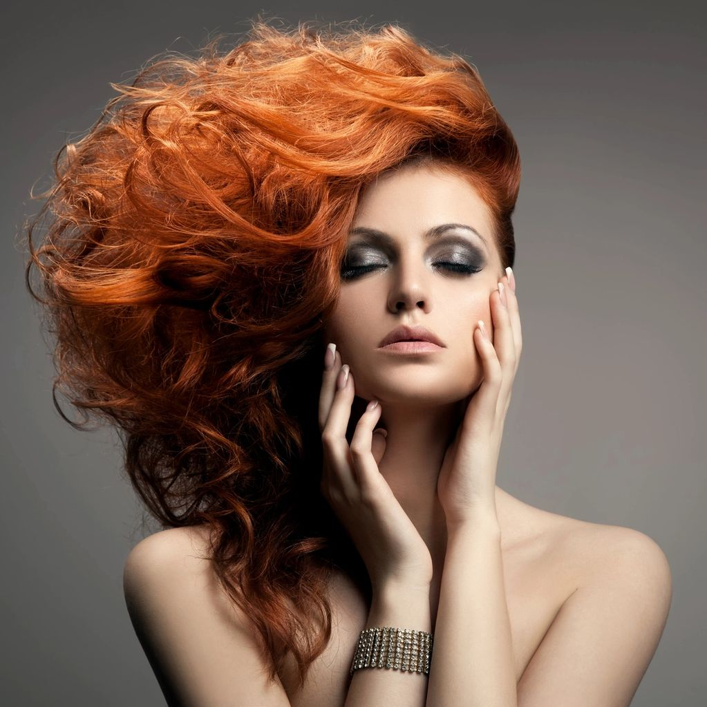 Face of female model with beautiful red hair and makeup.