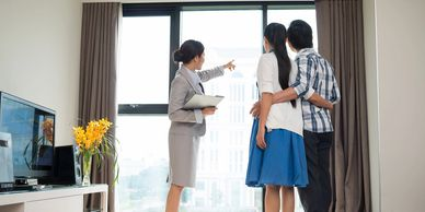 Realtor ® showing location to prospective buyers, a man and woman.
