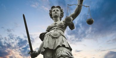 Statue of Lady Justice holding a sword in one hand and a balance in the other.