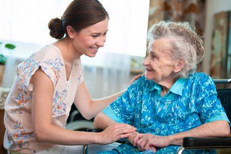 Home Health Aide assists a senior with Parkinson;s disease.