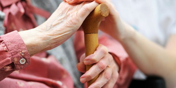 An elderly woman holding a walking stick