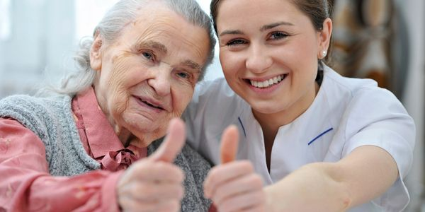 Client and Caregiver hold their thumbs up, smiles on their faces depicting trust between them.