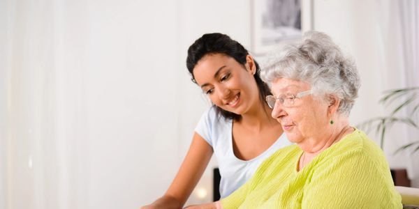 Image of a younger woman helping an older woman.