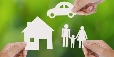 Person's hands holding cut-out of a house, car and family