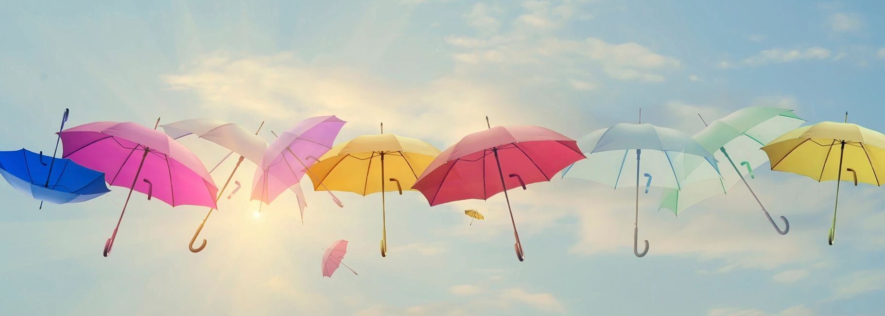 A row of ten multicolored umbrellas floating high on a mostly clear blue skied sunny day.