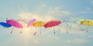 umbrella insurance image of multiple colorful umbrellas foating in a blue sky