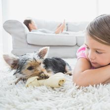 Kid and dog laying on carpet.