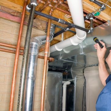 Home Inspector checking over pipes during home inspection.