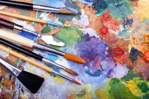paint brushes on multicolored abstract painting