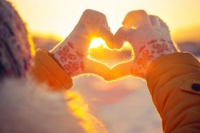 Hands making a heart pointing at the sun on a cold day. Signifies a love for life.