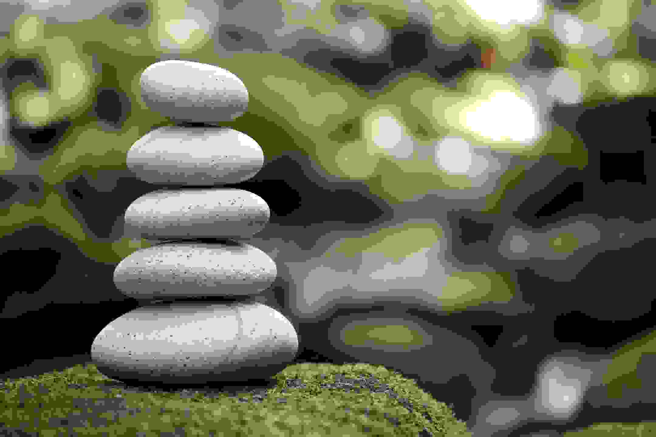 5 smooth and round stones piled vertically on a big mossy stone representing stress mangement for ti