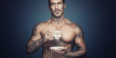 Sexy tattooed man drinking tea