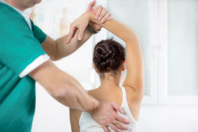 Chiropractor performing chiropractic service on hands and shoulder