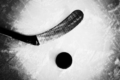 A hockey stick blade, taped, next to a puck on the ice, in a bright spotlight