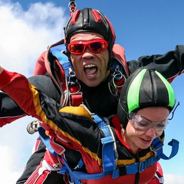 MAN AND WOMAN SKY DIVING MAN IS SCREAMING WOMAN IS CALM AND ENJOYING THE EXPERIENCE.