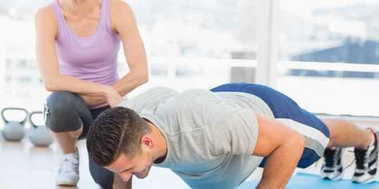 female personal trainer motivating male client doing push ups