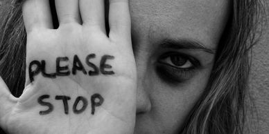 A girl with her hand held up in front of her face with the words PLEASE STOP written on it. Depicting domestic violence