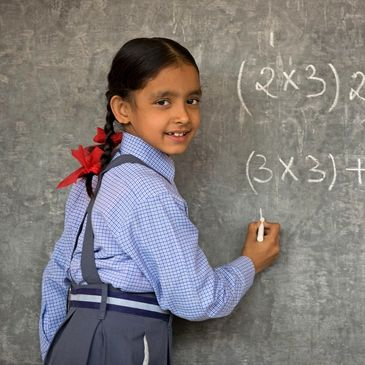 Little girl with bow in braided hair doing math