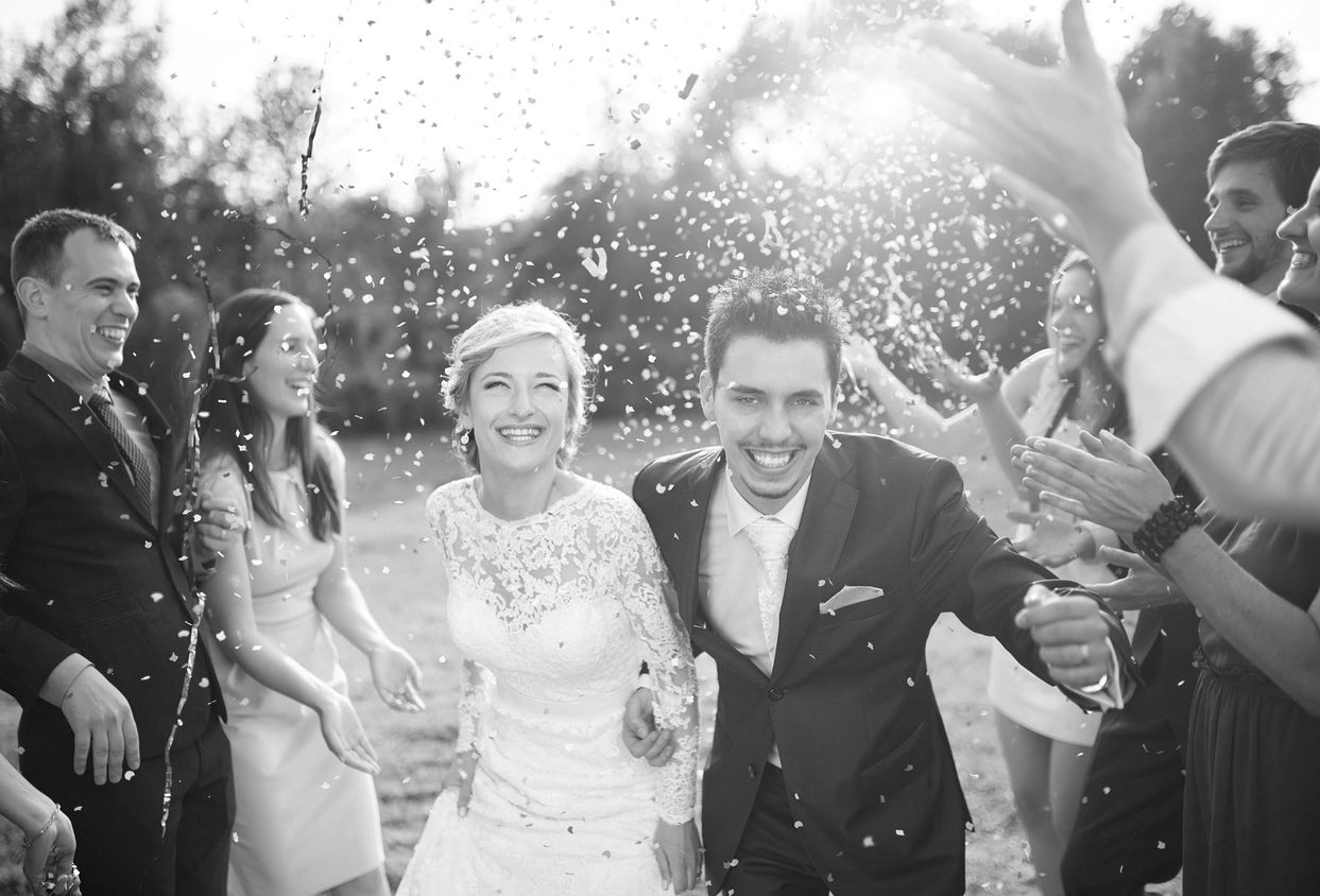 Newly married couple enjoying the moment as guest shower them with birdseed