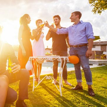 Friends drinking wine outdoors at sunset wearing smart casual attire on grass lawn