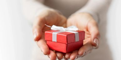 A woman extending her hands holding a small red gift box tied with a white bow.