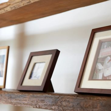 Three picture frames on a timber shelf