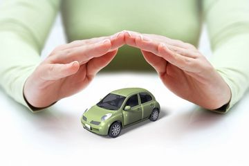 hands of an independent insurance agent covering a model green car