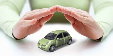 Auto insurance image of a small green car under a person's hands signifying coverage for the vehicle