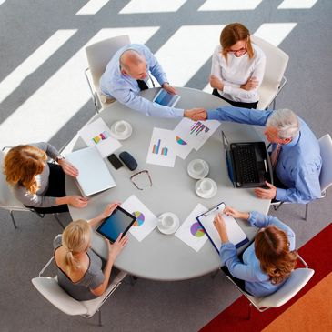 6people gathered around a round table covered in papers, a labtop and tablet