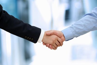 two men shaking hands, collaborating in workplace