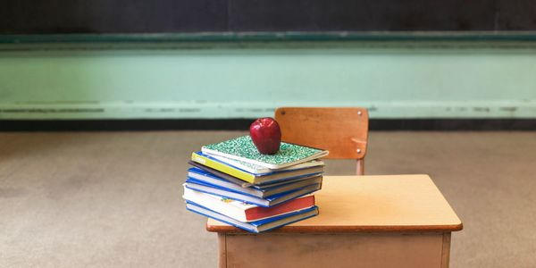 NDIS School Leavers- image of a school desk, a pile of books with a red apple on top.