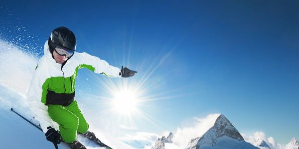 A skier skiing down a very steep slope and the sun and mountains creating a beautiful backdrop